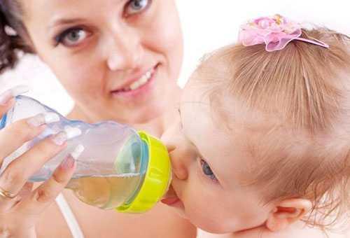 Маленькая девочка пьет отвар из бутылочки