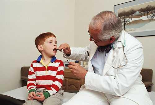 Осмотр горла ребенка педиатром