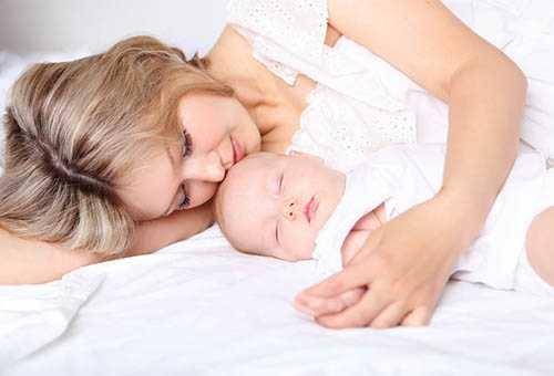 Молодая мама со спящим малышом