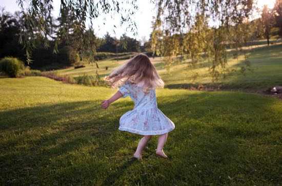 Девочка кружится на полянке