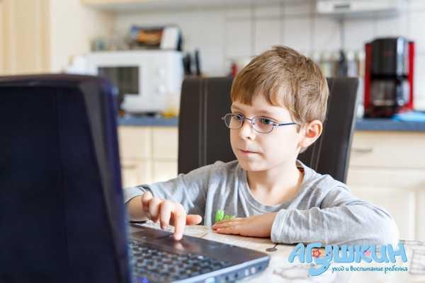 Ребенок в очках сидит за компьютером